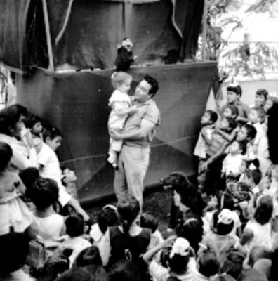Niño abrazando un muñeco de teatro guiñol, en una guardería del IMSS