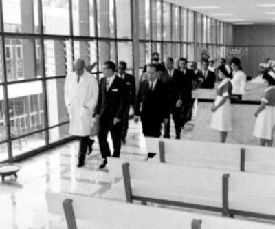Adolfo López Mateos, funcionarios y médicos recorriendo sala de espera de la clínica del IMSS Unidad Revolución durante su inauguración