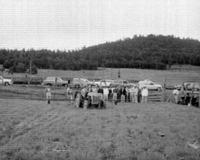 Funcionarios de la Secretaría de Agricultura observando una trilladora en un campo de cultivo
