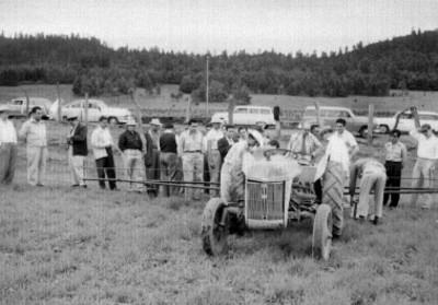 Agricultores mostrando maquinaria agrícola, en un campo de cultivo