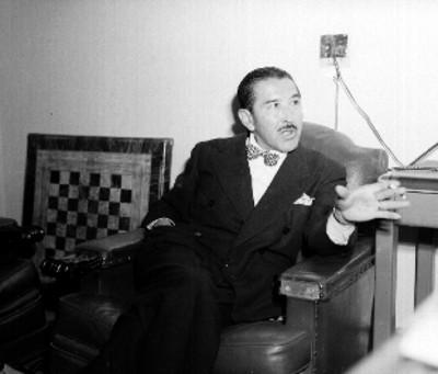 Varga, dibujante de la revista Hoy, sentado en el interior de una oficina