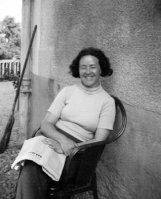 Carmen Carbo sentada con periódico en las manos, en el pasillo de una casa, retrato