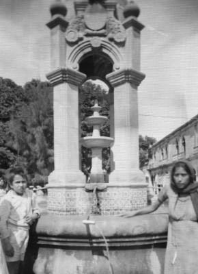 Mujer llenando cántaros con agua de una fuente