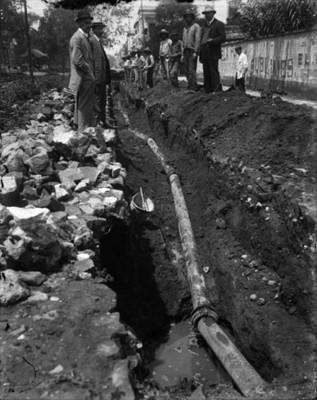Funcionario público con albañiles inspeccionando las obras de construcción del sistema de agua potable para el D.F.