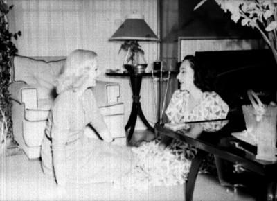 Miroslava conversando con una mujer sentadas en el piso de una sala