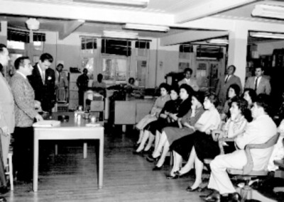 Empleados y empresarios reunidos en las oficinas de la General Electric durante una ceremonia