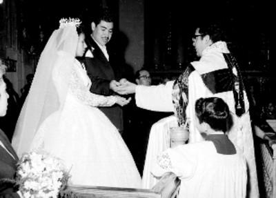 Novios ante un sacerdote entregando las armas, durante su boda religiosa