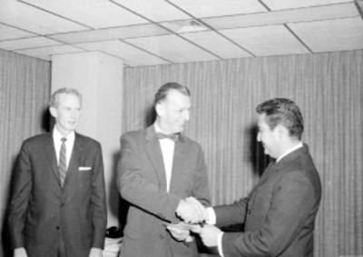 Empleado de la General Electric recibiendo un diploma durante una fiesta en casa del Sr. Calderón
