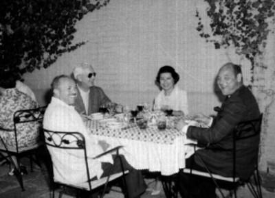 Banqueros y mujer sentados a la mesa de un jardín, durante una comida ofrecida por el Banco Nacional de México en Cuernavaca