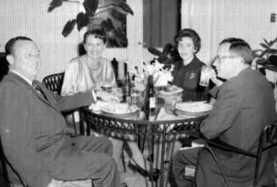 Ejecutivos con mujeres conviviendo en una cena en el University Club