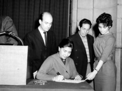 Empleada de los Laboratorios Pfizer, firmando una póliza de seguros durante una conferencia