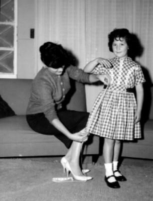 Modista tomando medidad a una niña, en una sala