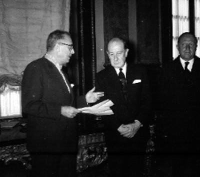 Manuel J. Tello conversando con miembros de la Cámara de Comercio en una sala