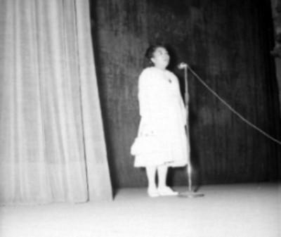 Alumna realizando una danza folclórica en un teatro, durante un festival escolar