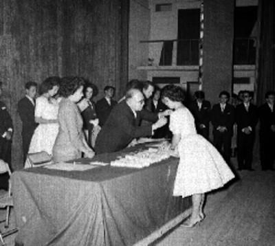 Alumno recibiendo una condecoración de un maestro, durante una ceremonia escolar