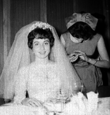 Novia acompañada por una mujer, sentada a la mesa, durante su festejo de bodas