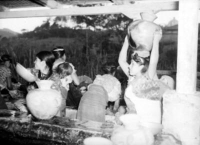 Indígenas llenando cantaros con agua de un pozo en una pareja de Guatemala