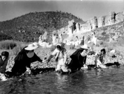 Monjas y Tarahumaras lavando ropa en la orilla de un río en un paraje