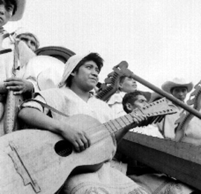 Músico tzotzil con el acordeón, acompañado por indígenas, durante la visita de Adolfo López Mateos a Oxchuc, retrato