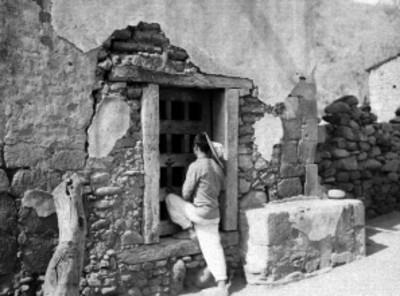 Indígena observando por la ventana de una casa en una comunidad de Durango