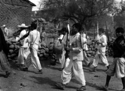Indígenas con bastones y músicos durante una procesión