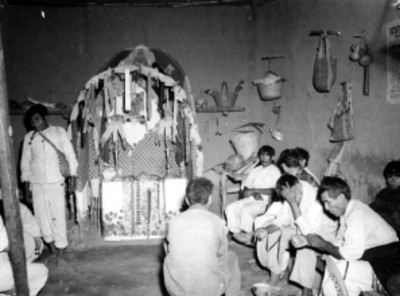 Indígenas frente a un altar religioso en el interior de una casa rústica en Nayar