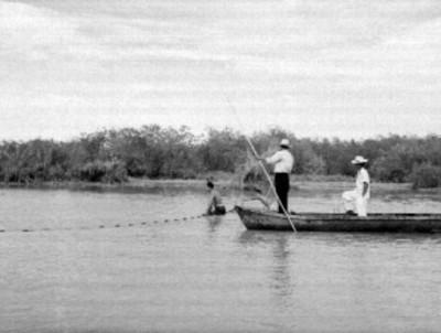 Hombres en una embarcación y pescadores trabajando, en una laguna de San Blás