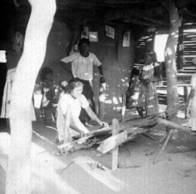 Mujer otomie tejiendo en un telar en el interior de un jacal