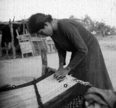 Mujer otomi tejiendo en un telar frente a un jacal