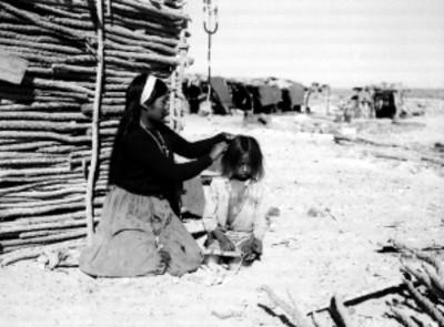 Mujer Seri peinando a un niño en una comunidad