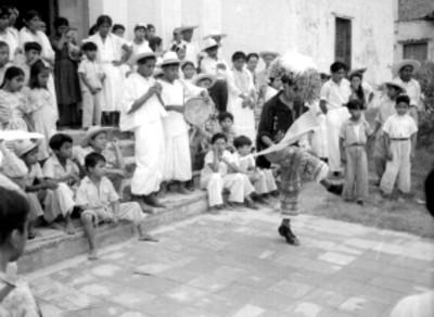 Danzante Totonaca bailando, acompañado por músicos en el atrio de la parroquia de Papantla