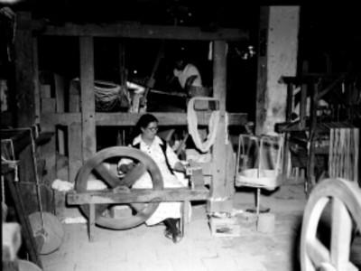 Mujeres trabajando con telares y una hiladora manual en un taller textil