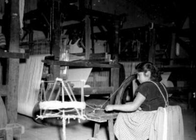 Mujer operando una hiladora manual en un taller textil