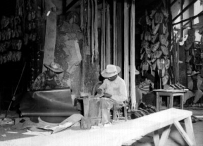 Zapateros curtiendo piel para la elaboración de huaraches