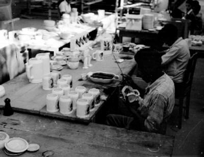 Artesanos pintando utensilios de alfareria en una fábrica de Tonalá