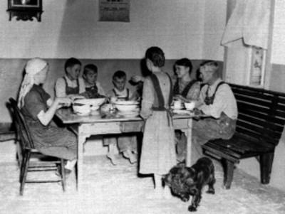 Familia menonita comiendo en la mesa, en el interior de una vivienda