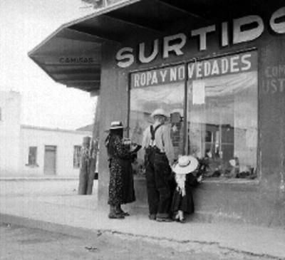 Familia menonita viendo el aparador de una tienda de ropa