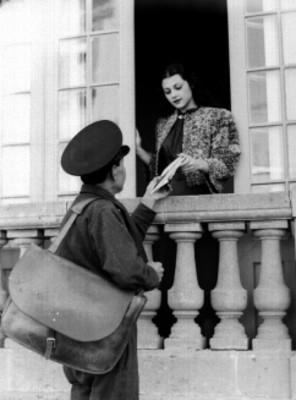 Esther Fernández en la ventana de su casa recibiendo correspondencia que le entrega un cartero