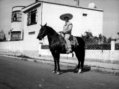 Francisco González de charro montado en caballo en la calle de un poblado, retrato