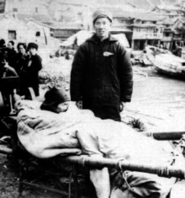 Soldado con herido en camilla durante la Segunda Guerra Mundial