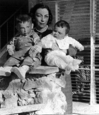 Mujer y sus hijos posando, junto a una ventana, retrato de familia