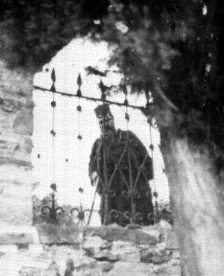 Sacerdote Ortodoxo asomando por una ventana con rejas en el Monte Athos en Macedonia