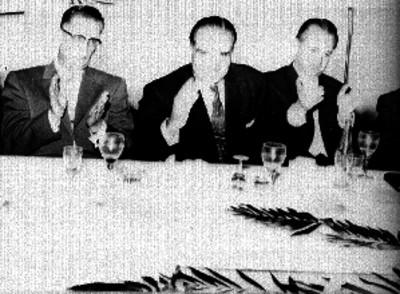Empresarios cinematográficos aplaudiendo durante un banquete en un salón
