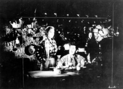 Actores en el interior de un jacal filmando la escena de una pelicula