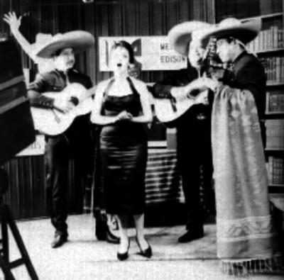 Mujer cantando ranchero, acompañada por mariachis, durante un programa de televisión