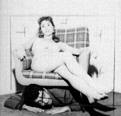Modelo con traje de baño sentada en un sillón y debajo de este hay un individuo