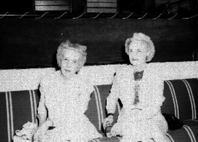 Mujeres sentadas en un sillón durante la convención del Variety Club, retrato