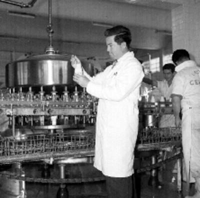 Químico revisando una botella de leche en polvo en una fábrica CEIMSA