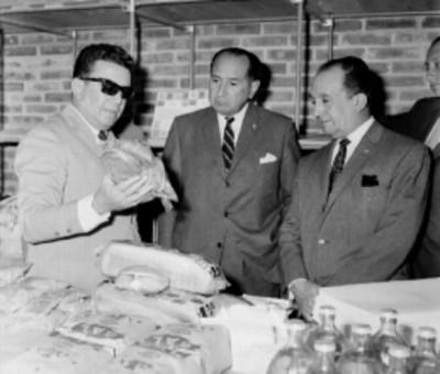 Roberto Amorós mostrando una botella de aceite elaborado por CONASUPO, a Mariano López Mateos y otro hombre