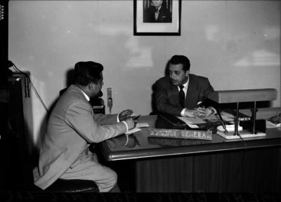 Antonio Mena Brito, sentado tras su escritorio, al parecer contestando una entrevista